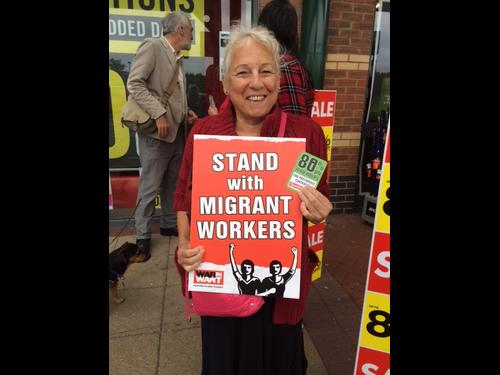 "Protestor holds a sign saying ""stand with migrant workers"" outside a Sports Direct shop in Newbury Credit: Carolyne Culver"