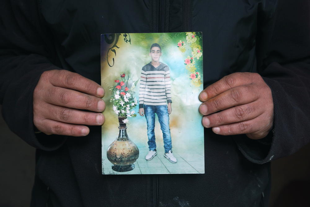 father holding a picture of his son Aziz