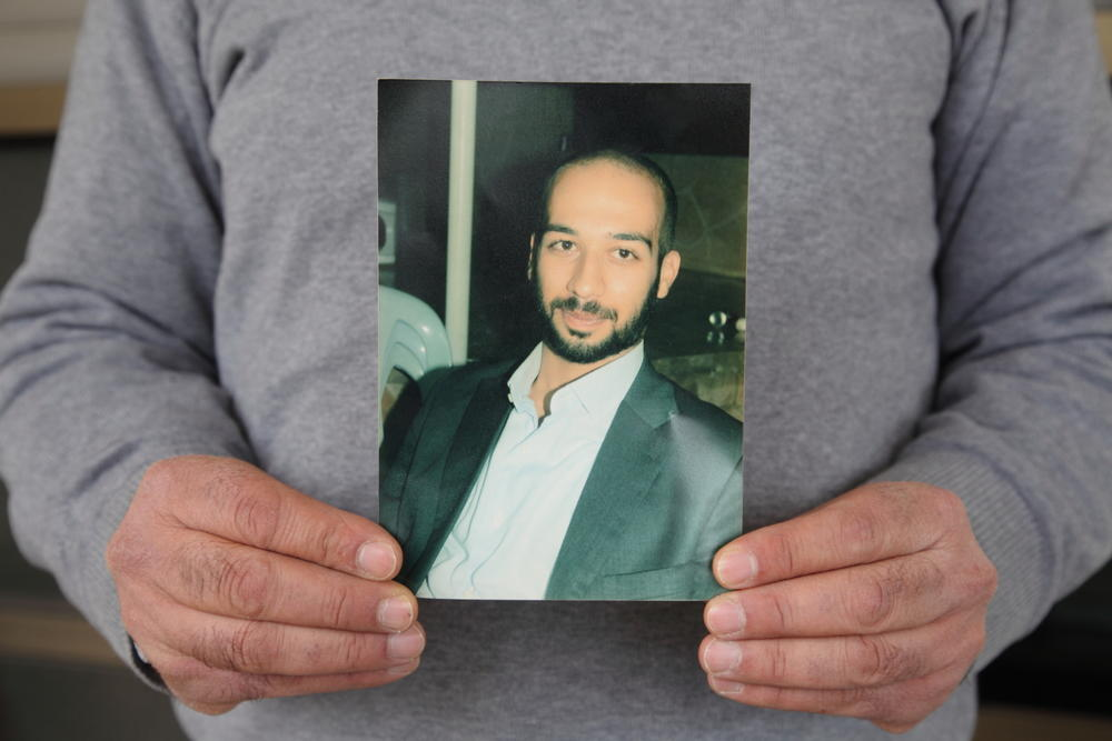 Abu Sakha's photo held by father