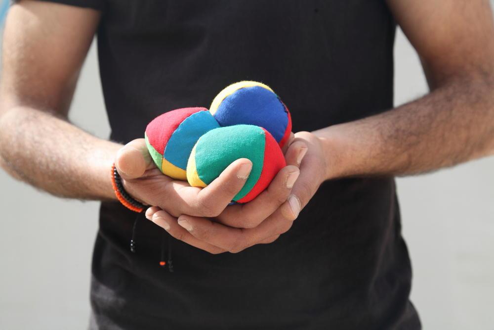 man holds juggling balls
